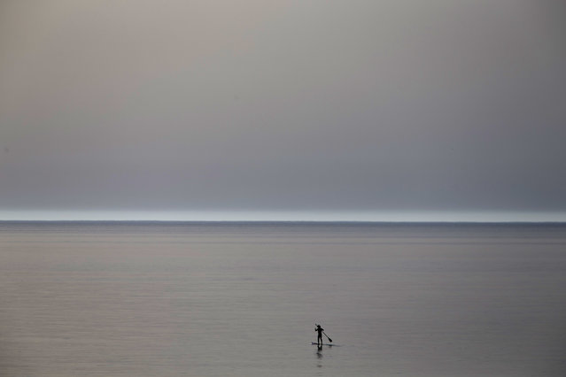 A surfer paddles in a peaceful and quiet Mediterranean sea near Beit Yanai, Israel, Tuesday, April 7, 2015, during the Passover holiday on a warm spring day. (Photo by Ariel Schalit/AP Photo)