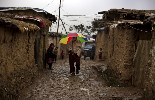 A man walks in the alley of a refugee camp in the suburbs of Islamabad, as temperatures dropped, on Wednesday, January 8, 2014. (Photo by B. K. Bangash/AP Photo)