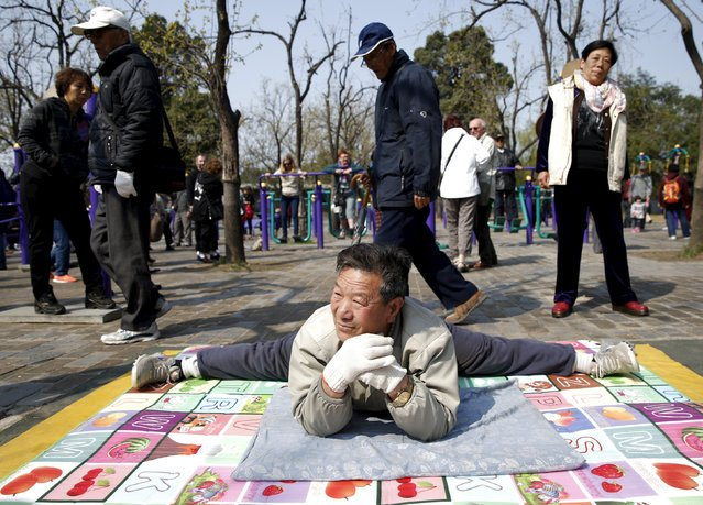 A man stretches out  at a park in Beijing April 13,  2015. (Photo by Kim Kyung-Hoon/Reuters)