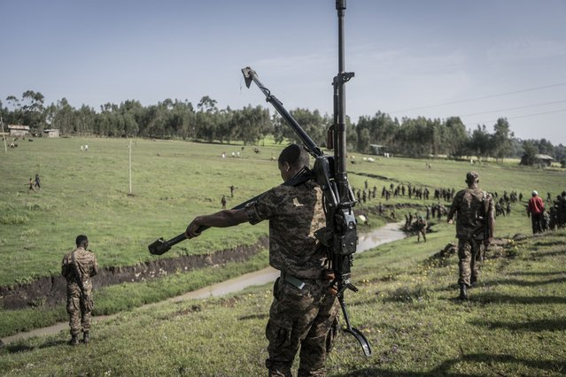 An Ethiopian National Defence Forces (ENDF) soldier carries a DShK 1938, a Soviet heavy machine gun, on his back during training in the field of Dabat, 70 kilometers Northeast of the city of Gondar, Ethiopia, on September 15, 2021. (Photo by Amanuel Sileshi/AFP Photo)