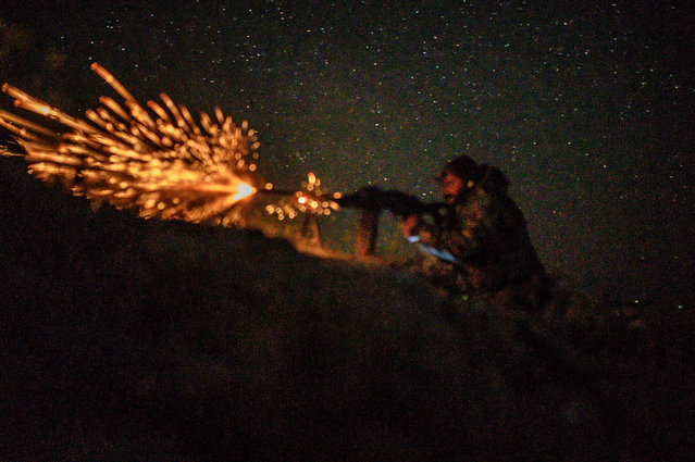 A fighter with the Syrian Democratic Forces (SDF) fires a machine gun in a position in the eastern Syrian province of Deir Ezzor outside the Islamic State group's embattled holdout of Baghouz , on March 11, 2019. Kurdish-led forces pounded the last scrap of land held by the Islamic State group in eastern Syria after hundreds more people surrendered. The jihadists once ruled over millions in a swathe of Syria and Iraq, but they have since lost all that territory except for a riverside slither of land near the Iraqi border. (Photo by Bulent Kilic/AFP Photo)
