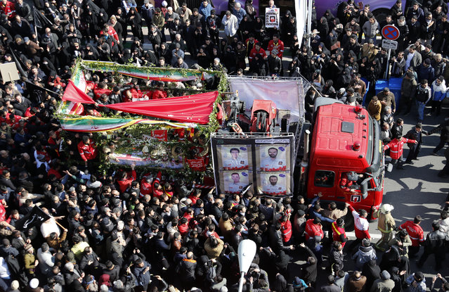 Iranians firefighters and mourners gather around a fire track carrying the coffins of firemen killed when the city's oldest high-rise collapsed after a blaze, during thier funeral ceremony in the capital Tehran on January 30, 2017. Tens of thousands of Iranians poured on to the streets of the Iranian capital for the funeral of firefighters killed when the 15-storey Plasco building, home to a shopping centre and hundreds of clothing suppliers, collapsed two weeks ago while emergency services were still evacuating people from a huge fire. (Photo by Atta Kenare/AFP Photo)