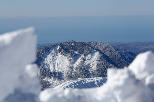 In this view from the top of a mountain, the Black Sea stretches out in the distance from near the start of the men's downhill ski course ahead of the 2014 Winter Olympics, Monday, February 3, 2014, in Krasnaya Polyana, Russia. (Photo by Alessandro Trovati/AP Photo)