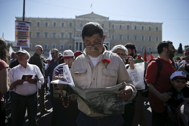 A man wearing a carnation at his lapel reads a newspaper during a May Day rally in front of the parliament building in Athens May 1, 2015. (Photo by Alkis Konstantinidis/Reuters)