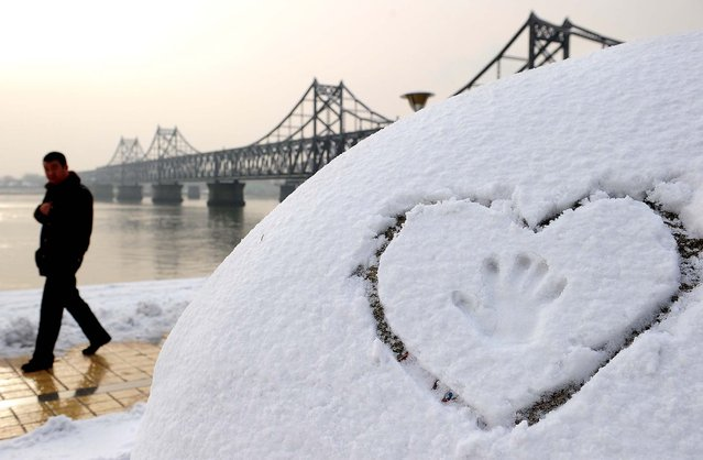 A man walks past an imprint of a hand in a heart drawn in the snow by the banks of the Yalu River in Dandong, China. (Photo by Frederic J. Brown/AFP Photo)
