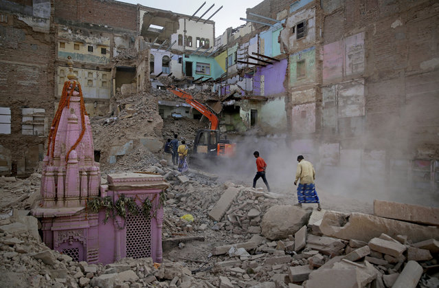 In this March 19, 2019, photo, locals walk past workers demolishing a house at the site of a proposed grand promenade connecting the sacred Ganges river with a centuries-old temple dedicated to Lord Shiva, in Varanasi, India. A project in the ancient Indian city of Varanasi dreamed up by Prime Minister Narendra Modi shows the master political marketer's penchant for symbolism as political strategy in elections that begin this month. (Photo by Altaf Qadri/AP Photo)