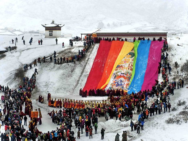 Visitors and Tibetan monks look on as a giant thangka, a religious silk embroidery or painting displaying the Buddha portrait, is unveiled amid snowfalls at Langmu Lamasery in Gannan Tibetan Autonomous Prefecture, Gansu province, on February 12, 2014. (Photo by Reuters/Stringer)