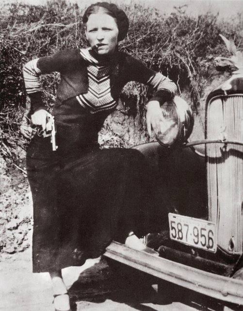 Full-length portrait of American criminal Bonnie Parker (1910 – 1934) smoking a cigar while leaning on the front fender of a car and holding a pistol on April 17, 1933. (Photo by Hulton Archive/Getty Images)