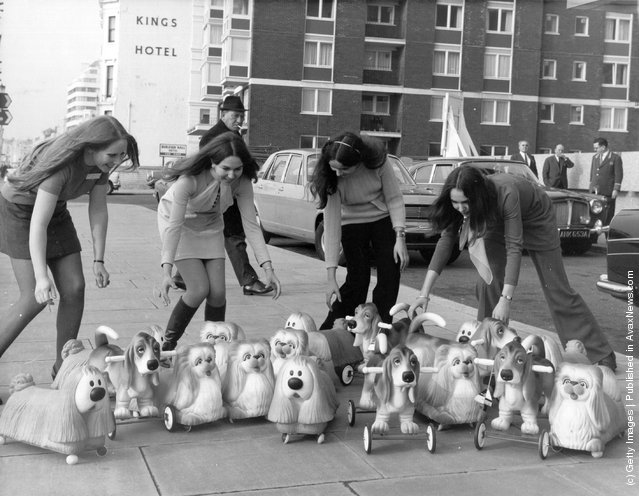 Toy rubber dogs, including several models of Dougal from The Magic Roundabout being demonstrated by four young women, on the pavement outside the Brighton Toy Fair, 1969