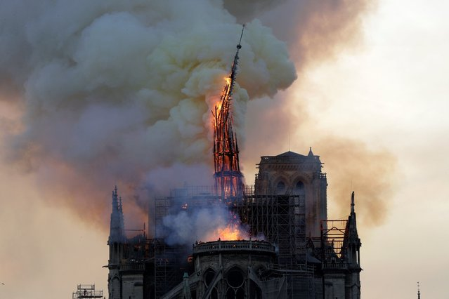 The steeple of the landmark Notre-Dame Cathedral collapses as the cathedral is engulfed in flames in central Paris on April 15, 2019. (Photo by Geoffroy Van Der Hasselt/AFP Photo)