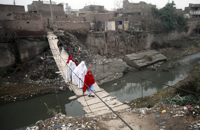 Villagers cross a makeshift bridge in a suburb of Peshawar, Pakistan, Monday, February 4, 2019. The previous bridge was washed away in a flood. (Photo by Mohammad Sajjad/AP Photo)