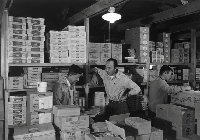 M. Ogi, S. Sugimoto, and Bunkichi Hayashi standing among shelves with boxes in a warehouse at the Manzanar War Relocation Center in California, 1943. (Photo by Courtesy Ansel Adams/Library of Congress, Prints and Photographs Division/Reuters)