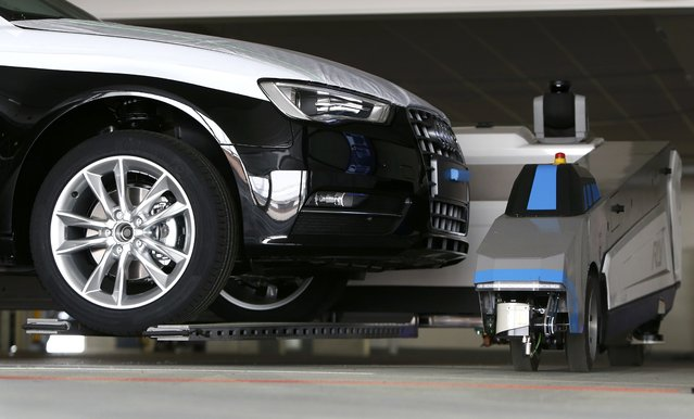 "Automated guided vehicle robot ""Ray"" lifts up an Audi car during a pilot project at the parking area of the Audi plant in Ingolstadt, Germany, May 13, 2015. (Photo by Michaela Rehle/Reuters)"