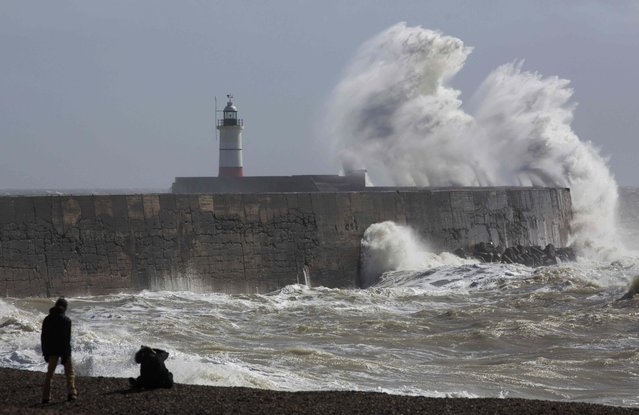 People watch waves crash against the harbour wall at Newhaven in southern Britain March 28, 2016. (Photo by Neil Hall/Reuters)