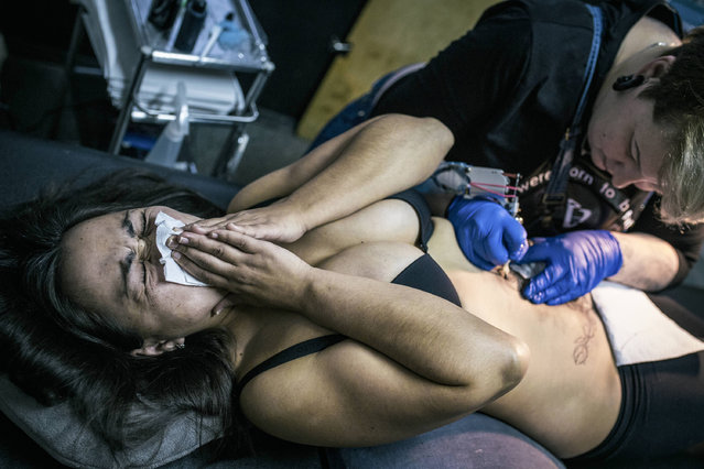 In this photo taken on Monday, December 5, 2016 Guldar, a victim of domestic violence, left, cringes from pain as artist Yevgeniya Zakhar works on her tattoo in Ufa, Russia. Yevgeniya Zakhar, a Russian tattoo artist from Ufa, a city about 1,200 kilometers (745 miles) east of Moscow, gives free tattoos to victims of domestic abuse, to cover their scars. (Photo by Vadim Braydov/AP Photo)