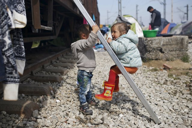 Children play along railway tracks at a makeshift camp for migrants and refugees at the Greek-Macedonian border near the village of Idomeni, Greece, March 29, 2016. (Photo by Marko Djurica/Reuters)