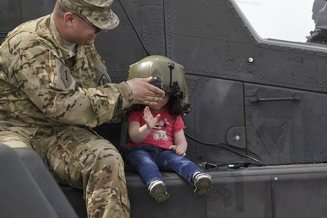 A US serviceman holds a pilot helmet for child posing on an Apache attack helicopter in Ploiesti, Romania, Wednesday, May 13, 2015. (Photo by Vadim Ghirda/AP Photo)