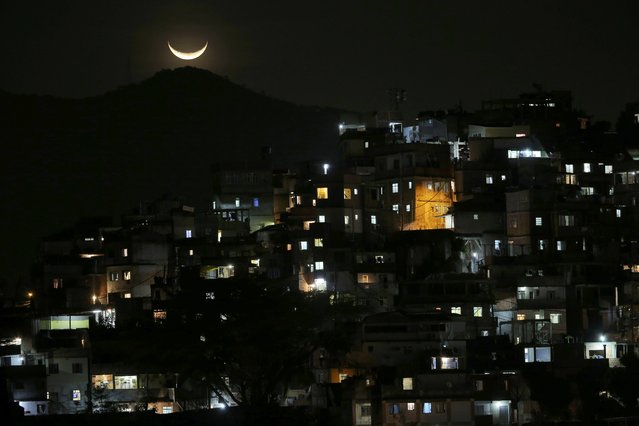 The moon is seen over a slum near Copacabana Beach in Rio de Janeiro, Brazil, August 6, 2016. (Photo by Carlos Barria/Reuters)