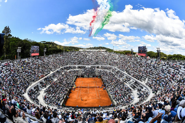 The Frecce Tricolori air squadron flies over the Foro Italico as Serbia's Novak Djokovic plays against Canada's Denis Shapovalov during their ATP Masters tournament tennis match in Rome on May 16, 2019. (Photo by Andreas Solaro/AFP Photo)