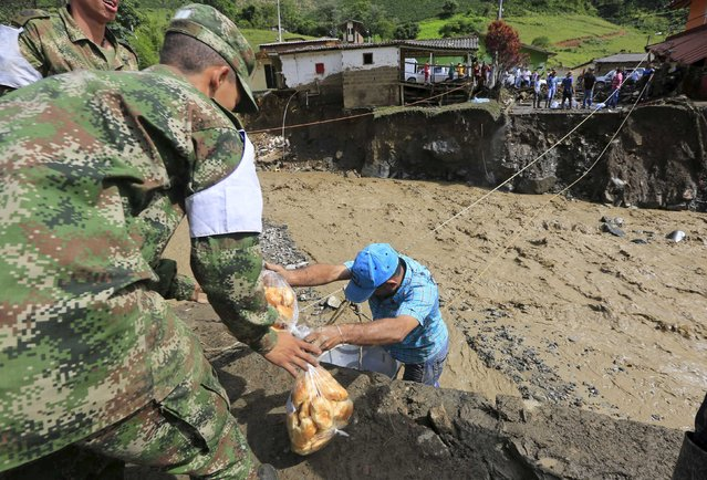 Colombian soldiers help collect food for residents who are victims of a landslide that sent mud and water crashing onto their homes close to the municipality of Salgar in Antioquia department, Colombia May 19, 2015. (Photo by Jose Miguel Gomez/Reuters)