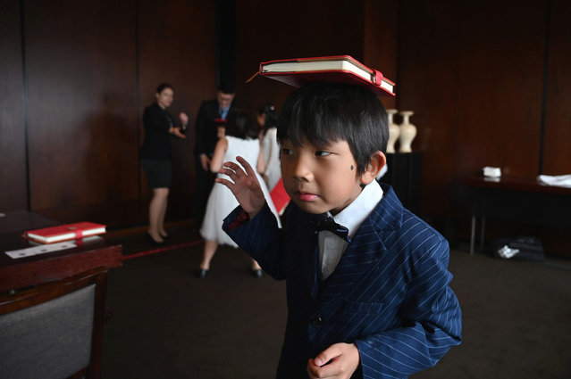This picture taken on June 1, 2019 shows Alex Gao trying to balance a book on his head during an etiquette and manners class in central Shanghai. (Photo by Hector Retamal/AFP Photo)