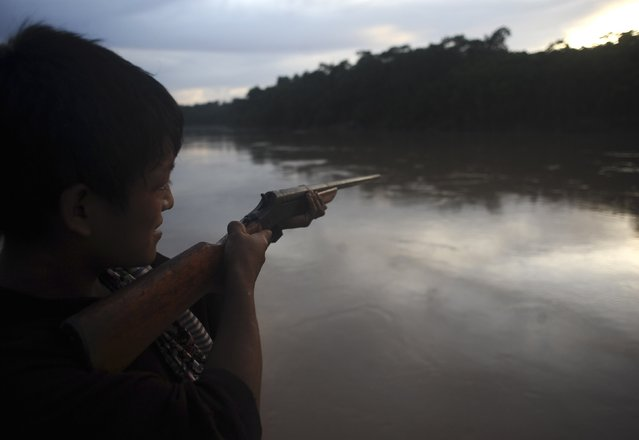 An Ashaninka Indian points his rifle across the Envira river on the grounds of a former government base called the Envira Front of Ethno-environmental Protection in Brazil's northwestern Acre state, March 14, 2014. (Photo by Lunae Parracho/Reuters)