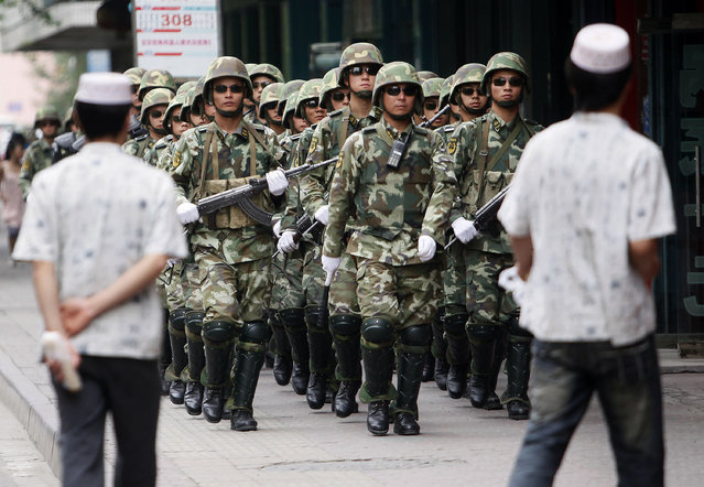 """In this Monday, July 13, 2009, file photo, paramilitary police officers patrol in the aftermath of riots as Uighur men walk by in Urumqi, western China's Xinjiang province. Analysts say the Urumqi riots in 2009 set in motion the harsh security measures now in place across Xinjiang, where about 1 million Uighurs, Kazakhs and other Muslims are estimated to be held in heavily-guarded internment camps – also called """"re-education"""" camps – which the Chinese government describes as vocational training centers. (Photo by Eugene Hoshiko/AP Photo/File)"""