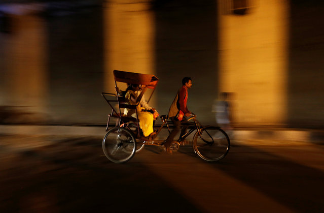 A man rides his rickshaw with passengers under a bridge in the old quarter of Delhi, India, April 19, 2016. (Photo by Adnan Abidi/Reuters)