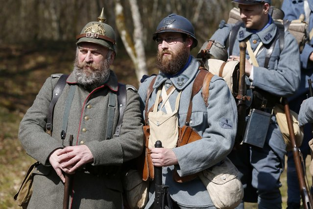 "Wolfgang (L), member of World War One historical association ""Darstellungsgruppe Suddeutsches Militar 1870-1918"" (DSM 18), from Munich, Germany, and Florent, member of French association ""Le Poilu de la Marne"", dressed in vintage army uniforms, visit the Bezonvaux bunker in the national forest of Verdun, eastern France, March 29, 2014. (Photo by Charles Platiau/Reuters)"