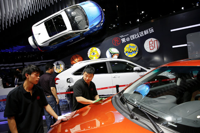 Members of staff clean a vehicle presented at BYD booth during Auto China 2016 auto show in Beijing, China April 25, 2016. (Photo by Damir Sagolj/Reuters)