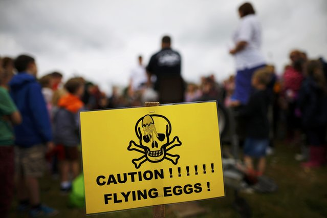 A warning sign stands near competitors playing Russian Egg Roulette during the World Egg Throwing Championships and Vintage Day in Swaton, Britain June 28, 2015. (Photo by Darren Staples/Reuters)
