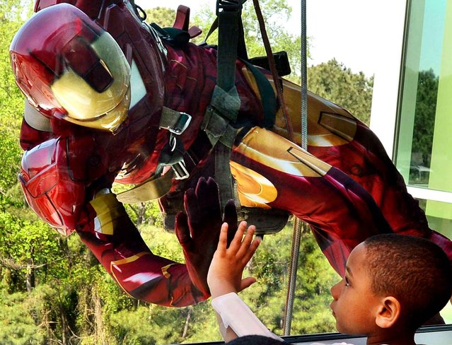 Lenox Barden, 5, gives a high five to Iron Man through a window on the fourth floor of WakeMed Children's hospital as three window washers dressed as Superheroes rappel down the side of the building Wednesday, April 16, 2014 in Raleigh, N.C. This was the second year that Batman, Iron Man and Spiderman have thrilled the children at the hospital. (Chuck Liddy/Raleigh News & Observer/MCT via Getty Images)