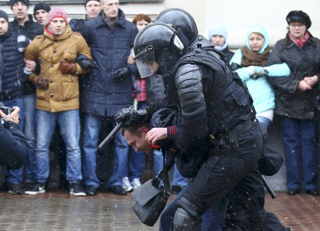 Law enforcement officers detain a man during a gathering, denouncing the new tax on those not in full-time employment and marking the 99th anniversary of the proclamation of the Belarussian People's Republic, in Minsk, Belarus, March 25, 2017. (Photo by Vasily Fedosenko/Reuters)