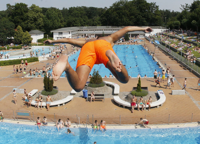 A young boy jumps from a 7.5 meter platform in an outdoor pool  in Frankfurt, Germany, Friday, July 3, 2015. The heat wave all over Germany will peak on Saturday with temperatures around 40 degrees  Celsius (104 Fahrenheit).  (Photo by Michael Probst/AP Photo)