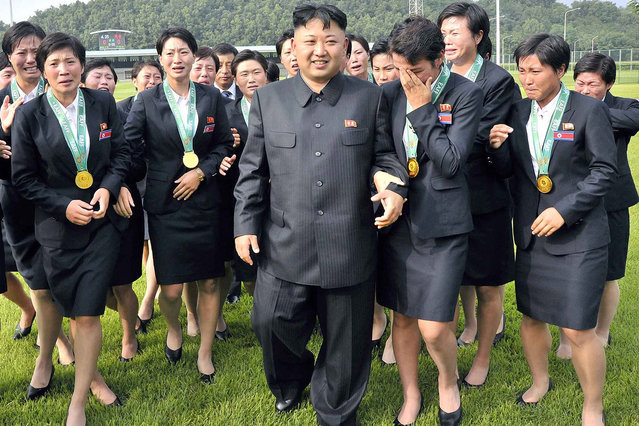 This recent undated photo released by North Korea's official Korean Central News Agency (KCNA) on August 1, 2013 shows North Korean leader Kim Jong-Un (C) meeting with members of the country's women's football team who won the recent 2013 East Asian Cup in South Korea. North Korea defeated China 1-0 in their final East Asian Cup women's match on July 27 in Seoul, and South Korea defeated Japan, allowing North Korea to win the regional event for the first time. (Photo by AFP Photo/KCNA via KNS)