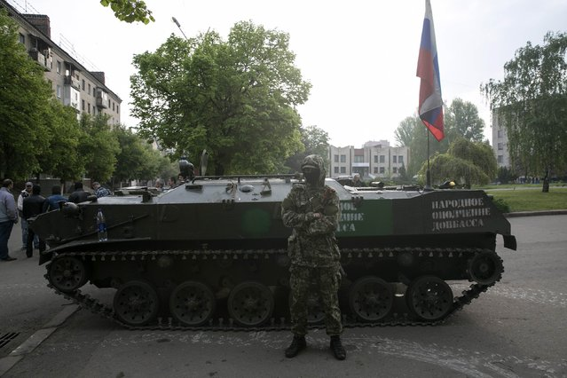 A pro-Russian separatist stands guard near an armoured personnel carrier in the town of Slaviansk in eastern Ukraine May 2, 2014. (Photo by Baz Ratner/Reuters)