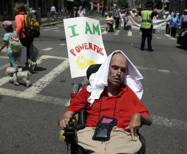 Gerard Mills tries to stay cool during the inaugural Disability Pride Parade, Sunday, July 12, 2015, in New York. The parade grand marshal was former U.S. Sen. Tom Harkin, the Iowa Democrat who 25 years ago sponsored the Americans With Disabilities Act. (Photo by Seth Wenig/AP Photo)