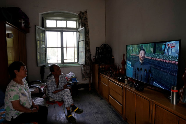 Residents watch on television Chinese President Xi Jinping reviewing troops at the military parade marking the 70th founding anniversary of People's Republic of China, from their home in Beijing, China on October 1, 2019. (Photo by Aly Song/Reuters)