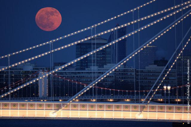 Full Moon Rises Over Albert Bridge In London