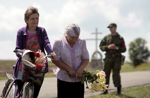 Women bring flowers as she attends a commemoration ceremony at the site of the Malaysia Airlines flight MH17 plane crash near the village of Hrabove in Donetsk region, Ukraine, July 17, 2015. The rebel-held east Ukrainian village where a Malaysian airliner was shot down honored the 298 victims at a simple ceremony on Friday as calls grew for an international tribunal to prosecute those who brought it down. (Photo by Kazbek Basaev/Reuters)