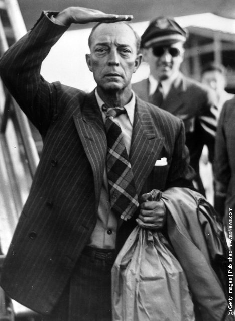 1947: Clutching a large paper bag and shading his eyes as he peers ahead, comic actor of the silent screen, Buster Keaton (1885 - 1966) arriving at Paris airport