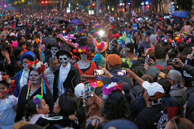 People dressed as Catrinas parade down Mexico City's iconic Reforma avenue during celebrations for the Day of the Dead in Mexico, City, Saturday, October 26, 2019. (Photo by Ginnette Riquelme/AP Photo)