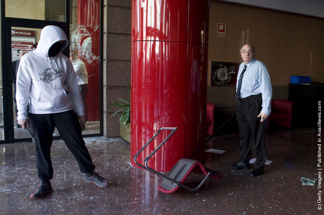 A Banco Popular bank employee faces a masked studend demonstrator after students broke into the bank branch  during a demonstration on February 29, 2012 in Barcelona