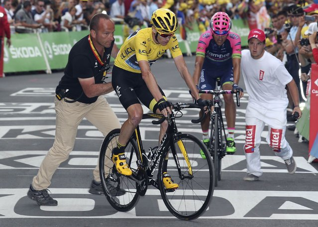 Team Sky rider Chris Froome of Britain, race leader's yellow jersey, is helped after crossing the finish line in the 161-km (100 miles) 17th stage of the 102nd Tour de France cycling race from Digne-les-Bains to Pra Loup in the French Alps mountains, France, July 22, 2015. (Photo by Stefano Rellandini/Reuters)