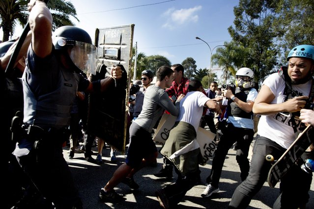 Police push back protesters and journalists in Sao Paulo, Brazil, Thursday, June 12, 2014. Brazilian police clashed with anti-World Cup protesters trying to block part of the main highway leading to the stadium that hosts the opening match of the tournament. (Photo by Rodrigo Abd/AP Photo)