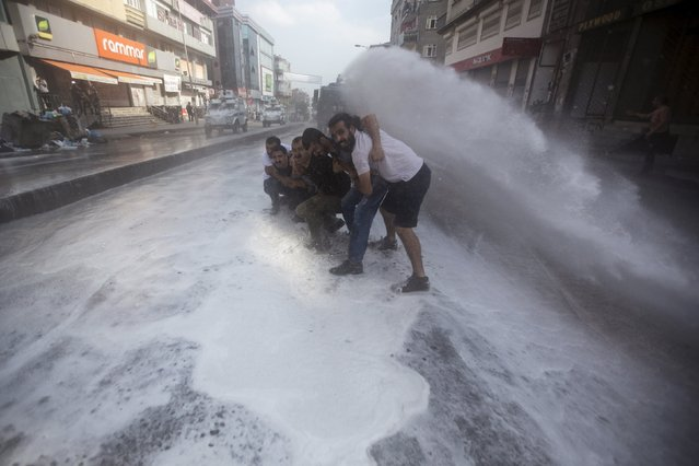 Turkish police use water cannon to disperse demonstrators during a funeral ceremony for Gunay Ozarslan, a member of far left People's Front who, according to local media reports, was killed by Turkish police during a security operation on Friday, in Istanbul, Turkey July 25, 2015. (Photo by Huseyin Aldemir/Reuters)