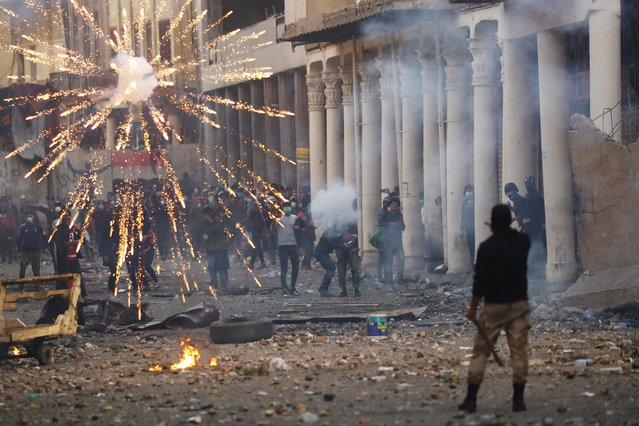 Iraqi demonstrators throw fireworks towards Iraqi security forces during the ongoing anti-government protests in Baghdad, Iraq on November 23, 2019. (Photo by Thaier al-Sudani/Reuters)