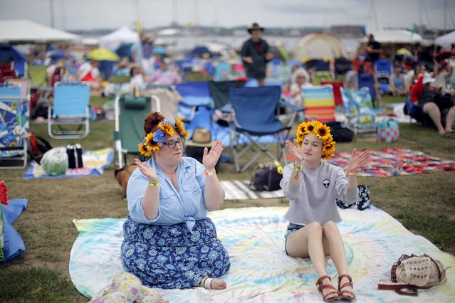 "Victoria Hillery (L) and Allison Taggerty listen to the performances at the Newport Folk Festival in Newport, Rhode Island July 26, 2015. This year marks the 50th anniversary of Bob Dylan's 1965 appearance at the Newport Folk Festival, when the up-and-coming folk star played with the backing of Mike Bloomfield on guitar and others from the electric blues/rock and roll band The Paul Butterfield Blues Band, marking Dylan's first live, electric, ""plugged-in"" set of his professional career. (Photo by Brian Snyder/Reuters)"