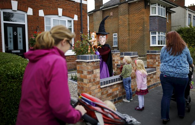 "Children look at a scarecrow of characters from the ""Room on a Broom"" book during the Scarecrow Festival in Heather, Britain, July 28, 2015. (Photo by Darren Staples/Reuters)"