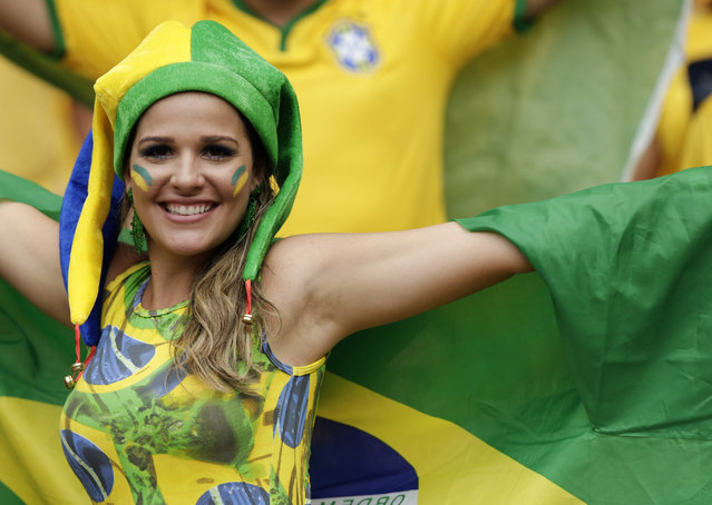 A Brazilian fan poses with her national flag before the group A World Cup soccer match between Brazil and Mexico at the Arena Castelao in Fortaleza, Brazil, Tuesday, June 17, 2014. (Photo by Marcio Jose Sanchez/AP Photo)